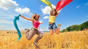 girls-jumping-on-a-wheat-field