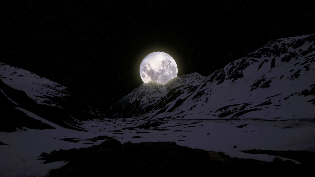 Moon leaning on mountaintops